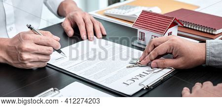 Real Estate Agent Are Presenting Home Loan And Giving Keys To Customer After Signing Contract To Ren