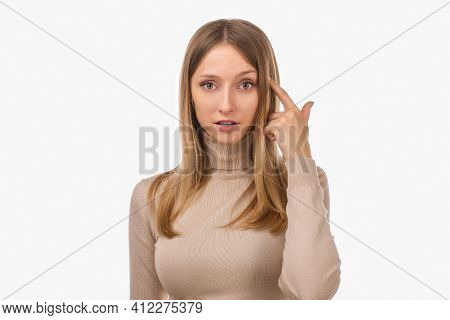Photo Of Thinking Young Woman With Blonde Straight Hair In Casual Clothes Pointing With Finger At He