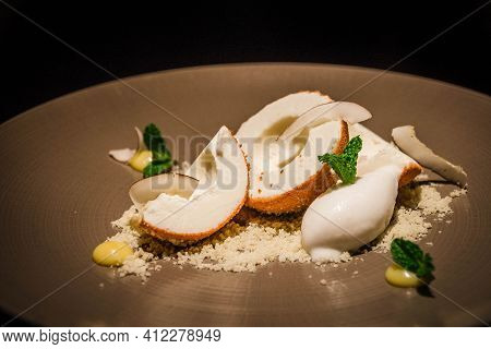 Coconut Ice Cream Served With Shaved Coconut, Dessicated Coconut And Mint On A Plate