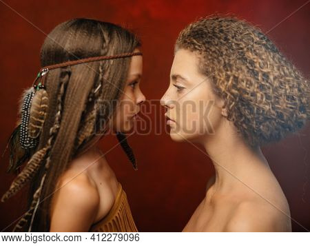 Beautiful Girl With A Feather In Her Hair And Woman Aborigines Red Background Family Indian Tribe