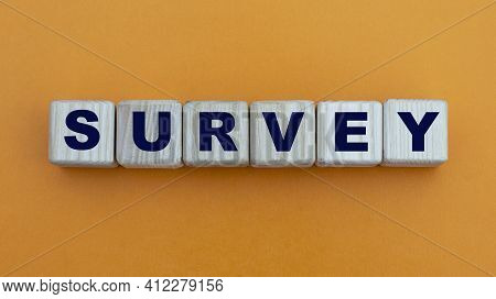 Survey - Word On Wooden Cubes On A Beautiful Yellow Background. Business Concept