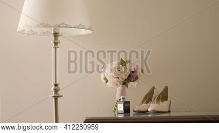 Table With Shoes And Flowers. Action. Delicate Interior With Floor Lamp, Table With Bouquet Of Flowe