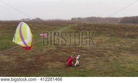 Beginning Of Paragliding, Instructor With A Red Superman Cloak And Client Starting To Fly. Action. P