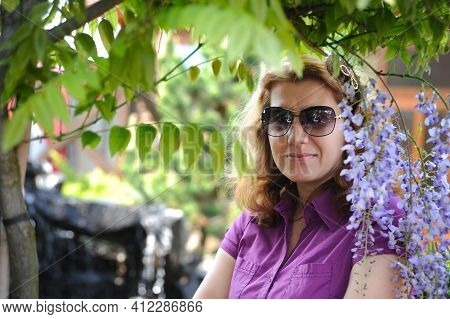 A Woman Wearing Resting Near A Green Tree And Beautiful Flowers. She Is Resting From The Hot Weather