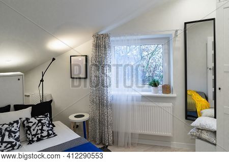 A Detail Of A Scandinavian Minimalist Style Interior. A Small Cozy Bedroom With A Bed, A Window And
