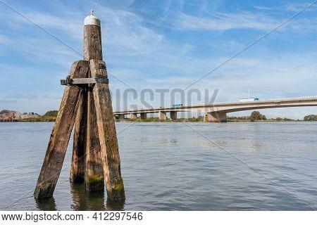 Dutch River Ijssel With Wooden Bollard And Concrete Road Bridge