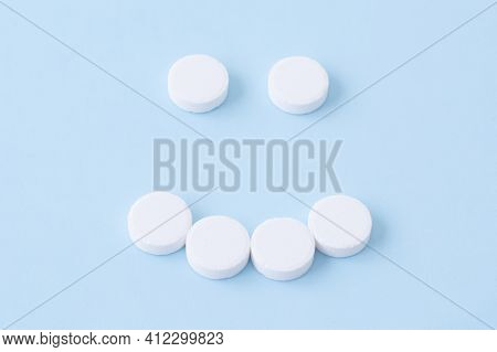 Smiling Face Made From White Round Pills On Blue Background. Medicine And Health Care Concept. Top V