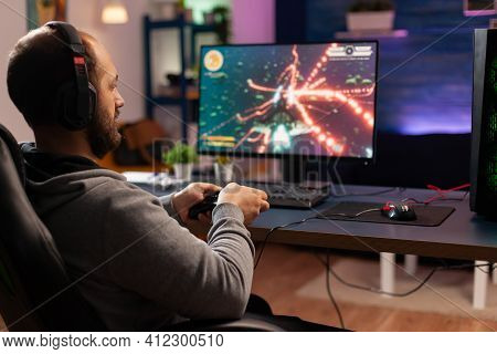 Concentrated Gamer Playing Virtual Game On Powerful Computer At Home With Professional Headphones. D