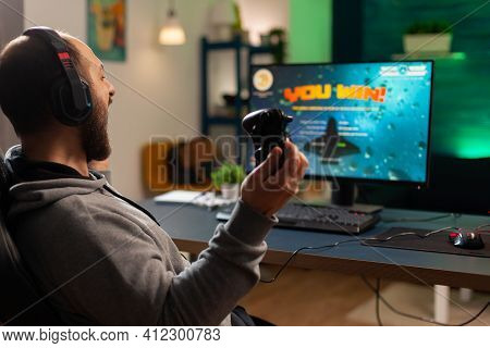 Videogame Player Raising Hands After Winning Space Shooter Competition Wearing Headset. Professional