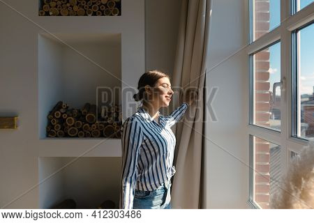 Young Caucasian Woman Opens The Curtains And Looks Out The Window On A Sunny Morning