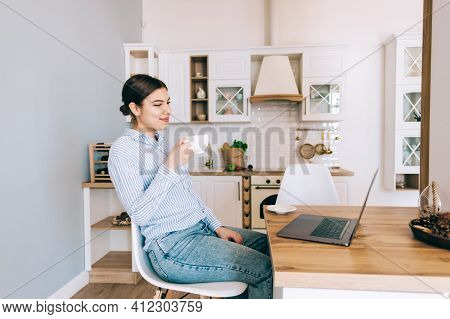 Young Caucasian Woman Drink Coffee And Using Laptop Computer While Sitting On Chair In Modern Kitche