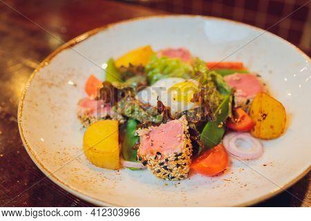 Seared Tuna Coated Sesame Seeds With Green Salad On White Plate.