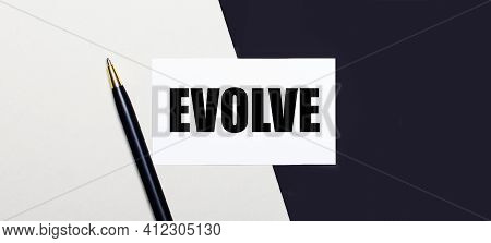 On A Black And White Background Lies A Pen And A White Card With The Text Evolve