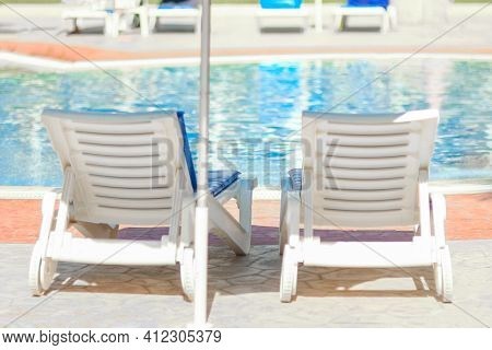 Beautiful Chaise Lounges By The Pool On Nature At Sea Background