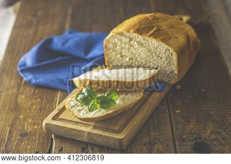 Loaf Of Freshly Baked Bread With Basil And Bread Slices On Wooden Board Over Rustic Wooden Table Bac