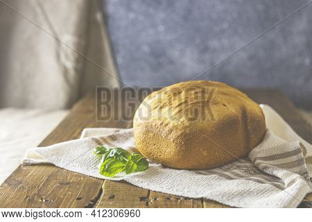 Loaf Of Freshly Baked Bread With Basil On Linen Towel Over Rustic Wooden Table Background. Selective