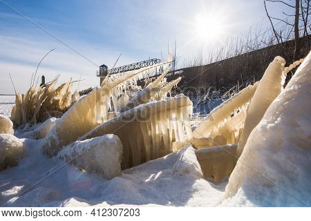 Ice Covered Plants In Freezing Lake Shore In Winter. Chilly Winter Afternoon At Seaside Promenade, S