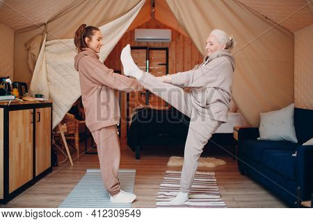 Family Doing Warming Up Exercises Sports Indoors. Young And Senior Elderly Woman Relaxing At Glampin