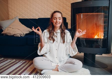 Portrait Of Young Woman Sitting In Lotus Position Indoors With Fireplace. Yoga And Meditation Zen Li
