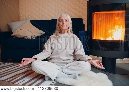 Portrait Of Senior Woman Sitting In Lotus Position Indoors With Fireplace. Yoga And Meditation Zen L