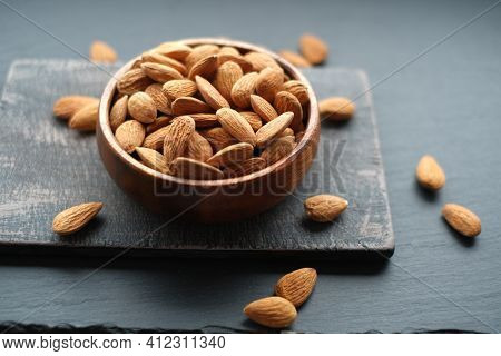 Almonds Nuts Close-up In A Cup On A Black Shabby Chic Board On A Black Schiffer Blurred Background.n