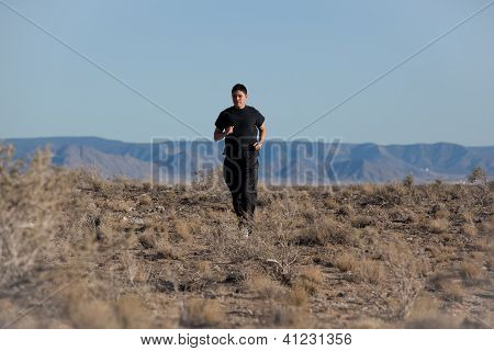 Athletic dark haired young man running in the desert on a hot sunny day poster