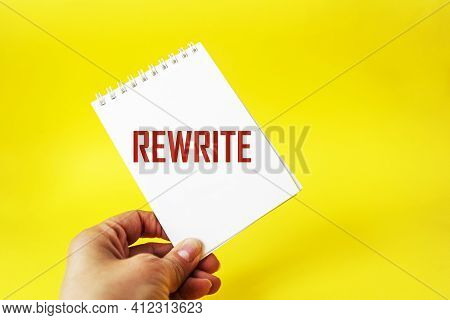 The Word Rewrite On A Notebook In A Female Hand And A Yellow Background