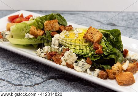 Wedge Salad With Fresh Vegetables Served On A Plate Topped With Croutons.