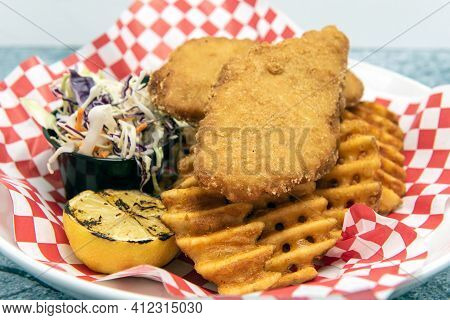 Fish And Chips Hot Of The Fryer Served With Waffle French Fries And Cole Slaw.