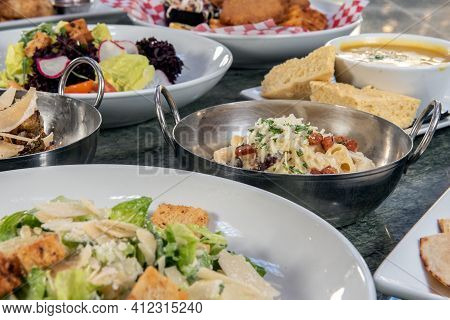 Full Table Of A Variety Of Restaurant Dishes To Choose From With Macaroni And Cheese Bowl In The Cen