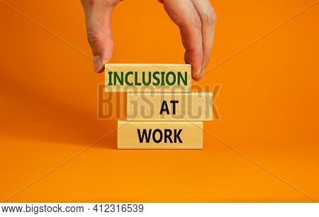 Inclusion At Work Symbol. Wooden Blocks With Words 'inclusion At Work' On Beautiful Orange Backgroun