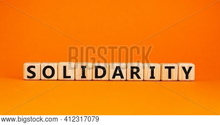 Time To Solidarity Symbol. Concept Word Solidarity On Wooden Cubes On A Beautiful Orange Background.