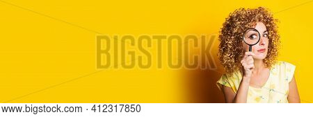 Curly Young Woman Looks Through A Magnifying Glass On A Yellow Background. Banner.