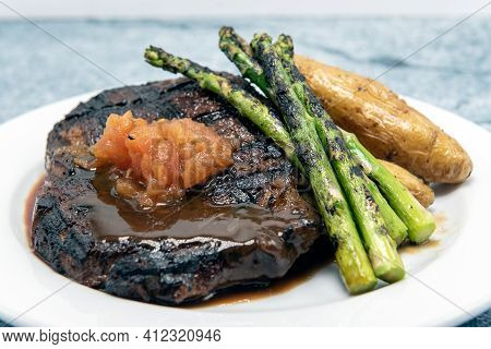 Grilled Rib Eye Steak Cooked To Perfection Served With Asparagus, Roasted Peppers, And Topped With A