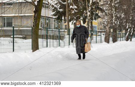 Lutsk, Ukraine - February 12, 2020: City Street After Blizzard. Woman Wearing Face Mask On Public St