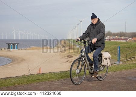 Urk, The Netherlands - February 19 2021: Senior Man At Bycycle Near Dutch Coast Of Urk, In The Backg