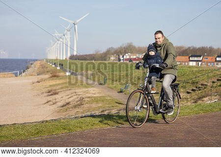 Urk, The Netherlands - February 19 2021: Father With Little Son At Bycycle Near Dutch Coast Of Urk,