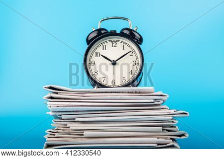 Newspapers And Black Alarm Clock On Blue Background. Retro Alarm Clock On Newspapers. Media News Tim