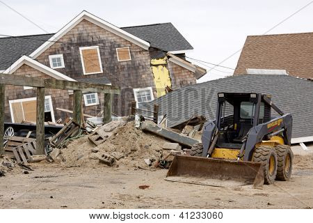 LAVALLETTE, NJ - JAN 13: A bulldozer in front of destroyed homes on January 13, 2013 in Lavallette, New Jersey. Clean up continues 75 days after Hurricane Sandy struck the shore in October 2012.
