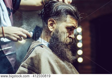 Bearded Male Sitting In Barber Shop While Hairdresser Shaves His Beard. Bearded Man Getting Powder O