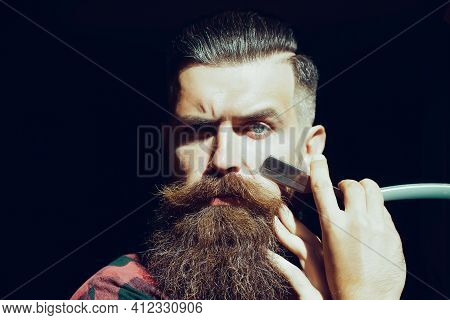 Close Up Beard And Mustache. Bearded Man Holding Razor With Serious Face. Bearded Client Visiting Ba