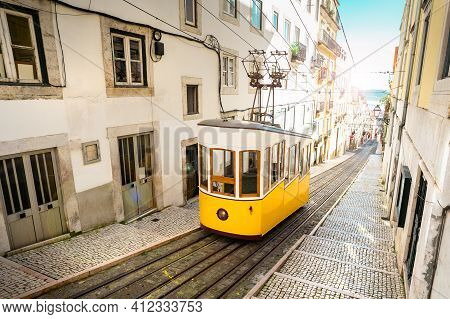 Lisbon City Old Town Narrow Streets And Tram, Portugal. Famous Retro Yellow Funicular Tram On A Sunn
