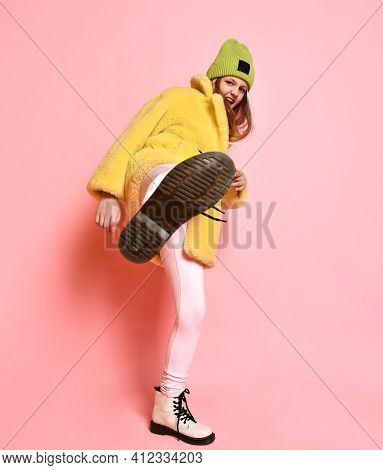 Bright Rebellious Girl Kicks The Camera While Standing On A Pink Background. Aggressive Teenager In