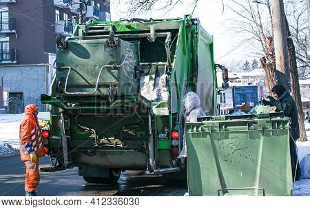 Dnepropetrovsk, Ukraine - 02.19.2021: Workers Of The City Municipal Garbage Collection Service Load