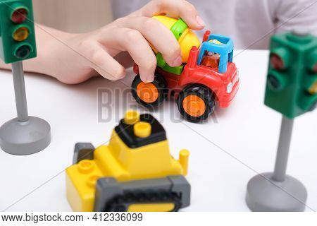 A Boy Playing Toy Cars On A White Table