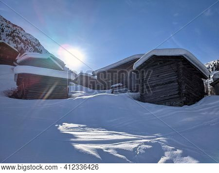 A Small Hamlet In Winter Above The Small Village Of Monstein In Davos. Sunny Winter Morning Landscap