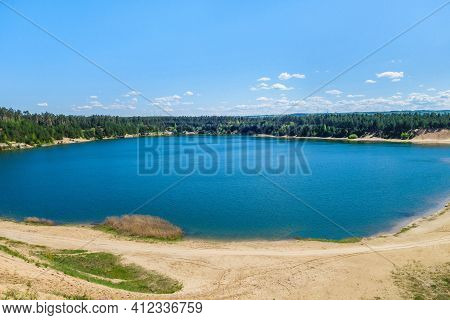 Dark Blue Lake Surrounded By Pine Forest. Lake Arose On Site Of Former Industrial Quarry