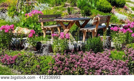Colorful spring garden with table and bench