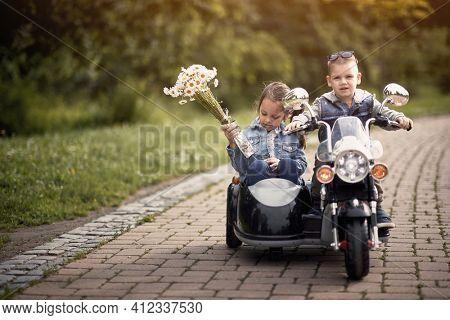 cute caucasian preschooler driving little girl in sidecar of motorcycle toy on battery in park