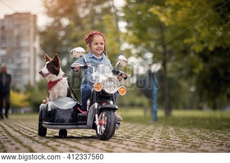 cute female preschooler driving electrical motorcycle toy with sidecar and her dog in it, smiling